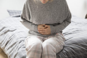 Sick woman in grey homewear sitting on bed, keeping hands on stomach, suffering from intense pain.