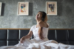 Woman sitting on a bed with neck pain