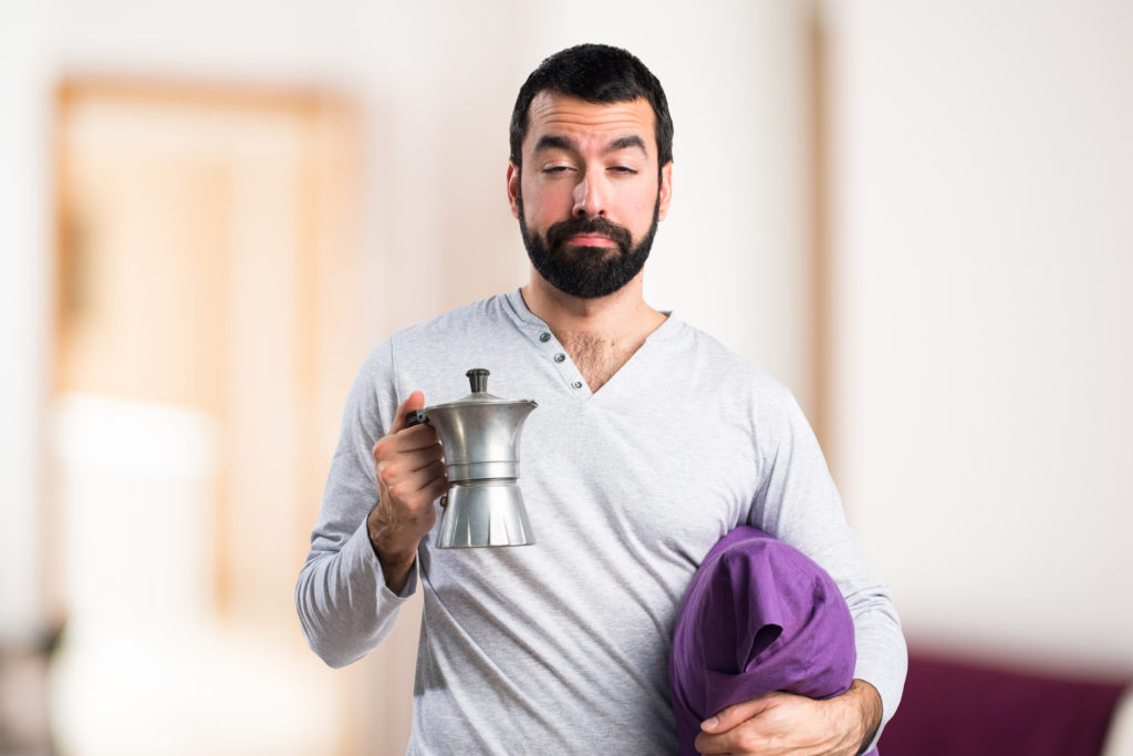 Man in pajamas holding a coffee pot